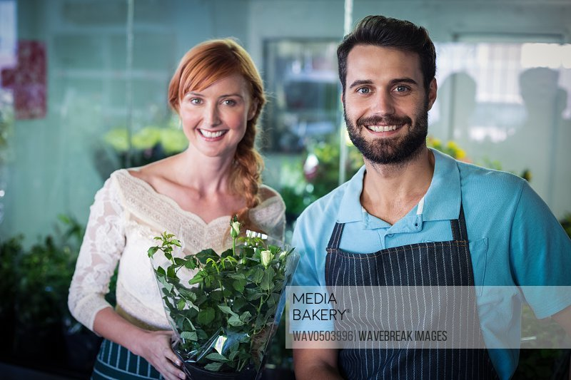 Happy couple holding flower bouquet in the flower shop