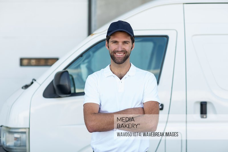 Portrait of delivery man standing with arms crossed in front of his van