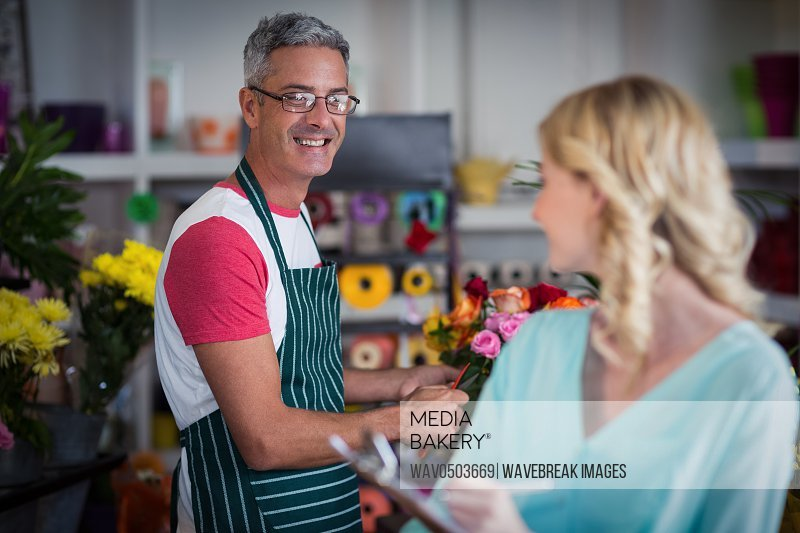Smiling florists interacting with each other at flower shop