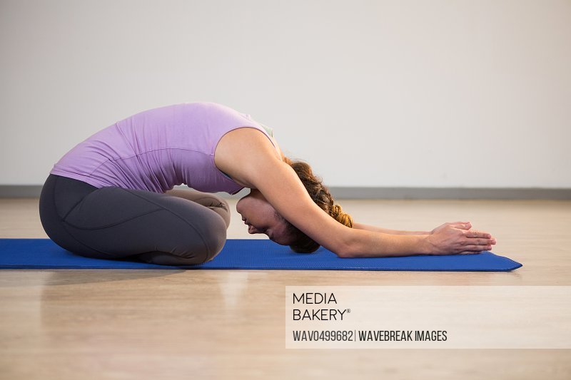 Woman doing yoga child pose on exercise mat in fitness studio