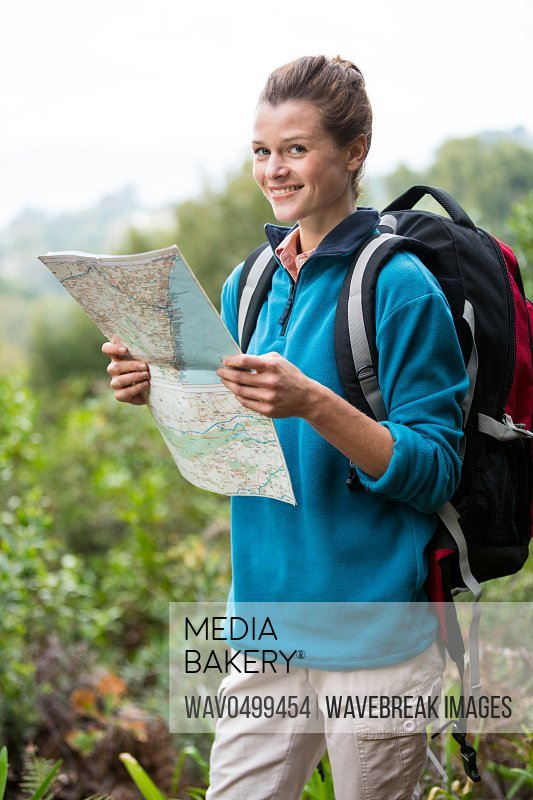 Portrait of smiling female hiker looking at map in forest
