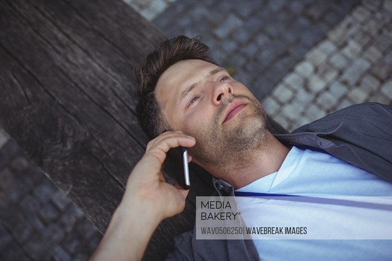 Handsome business executive lying on wood while talking on mobile phone