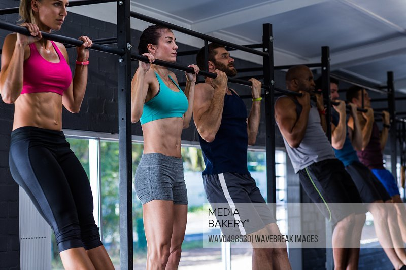 Young friends doing chin-ups while exercising in gym