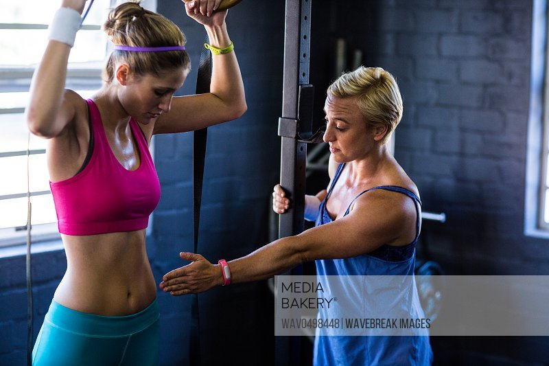 Female trainer instructing woman while standing in gym