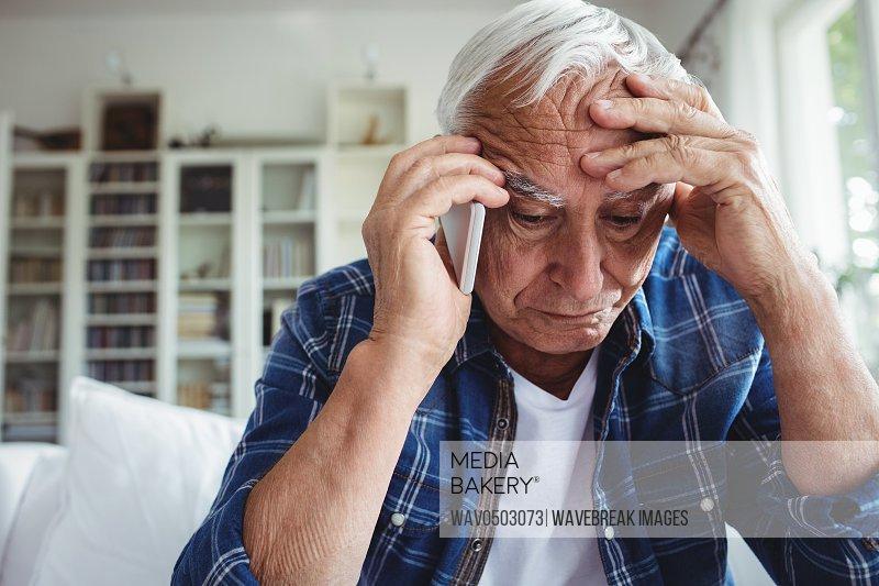 Tensed senior man talking on mobile phone at home