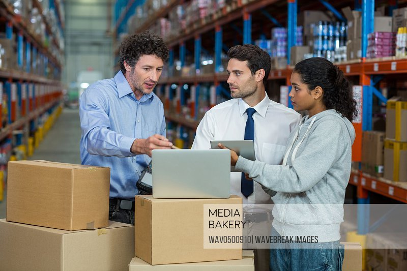 Warehouse manager and worker discussing with laptop in warehouse