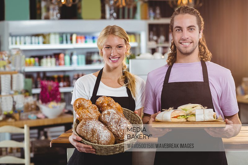 Portrait of waiter and waitress holding a tray of bread and meal in cafe