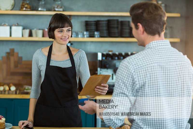 Smiling waitress giving parcel to customer at counter in cafe