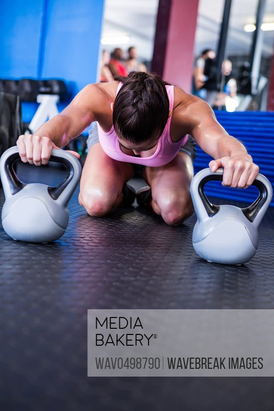 Female athlete with kettlebells while kneeling in gym