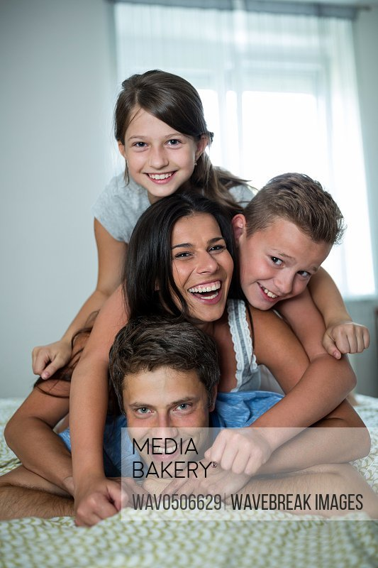 Portrait of happy family having fun in bedroom at home