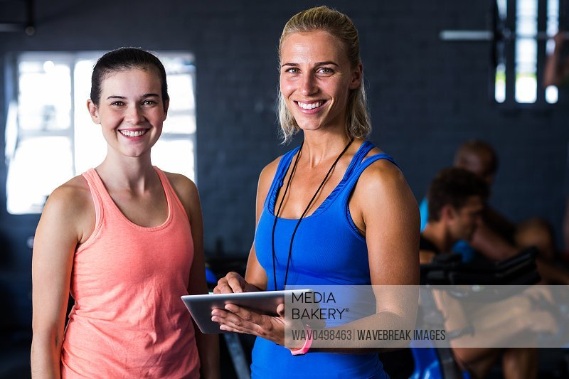 Portrait of happy friends with digital tablet while standing in gym