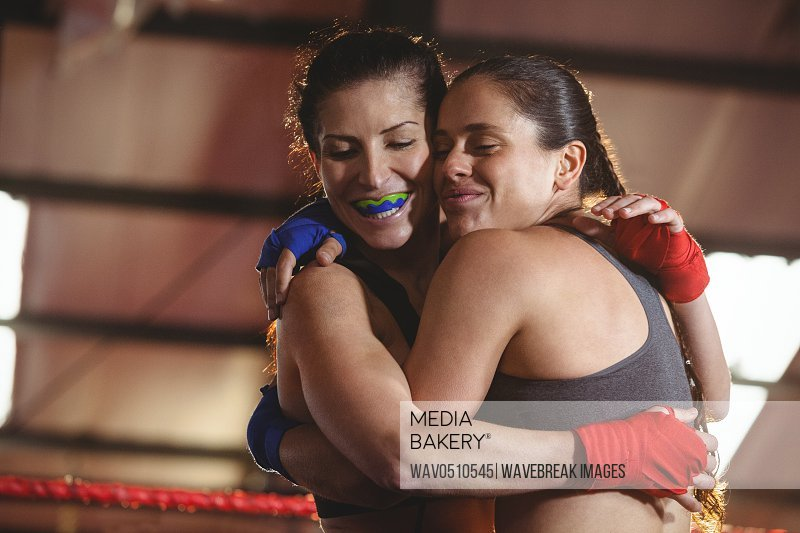 Two female boxers hugging each other in the ring at fitness studio