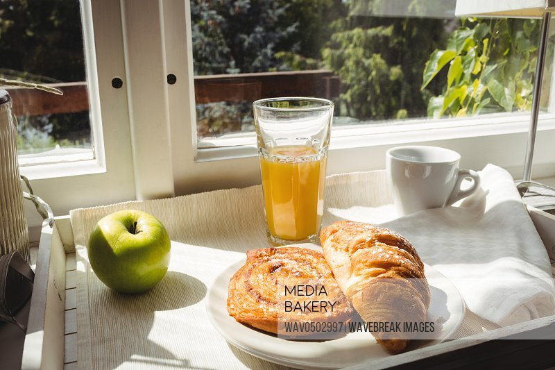 Close-up of croissant and glass of juice on a tray at home