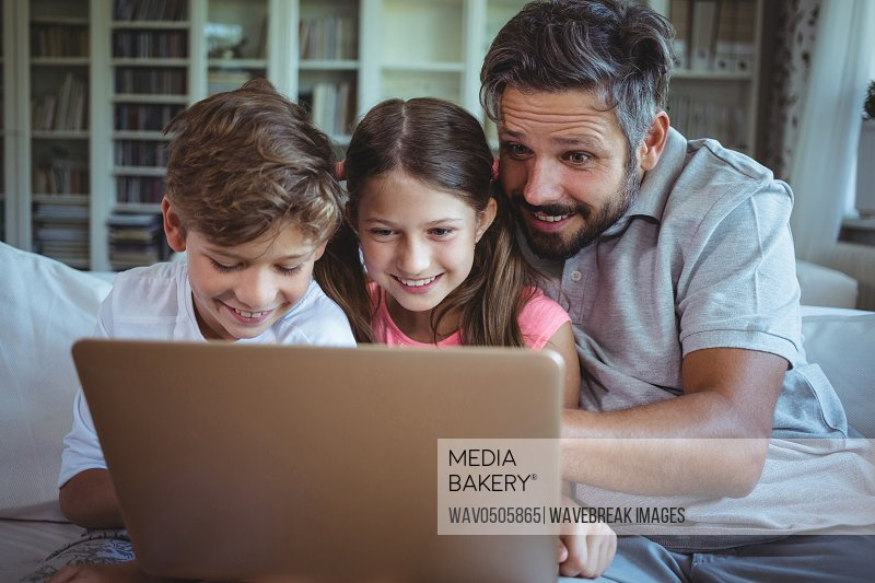 Father sitting on sofa with his children and using laptop in living room at home