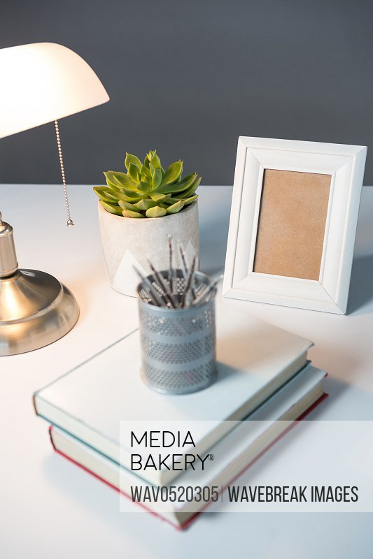 Table lamp picture frame and books on table