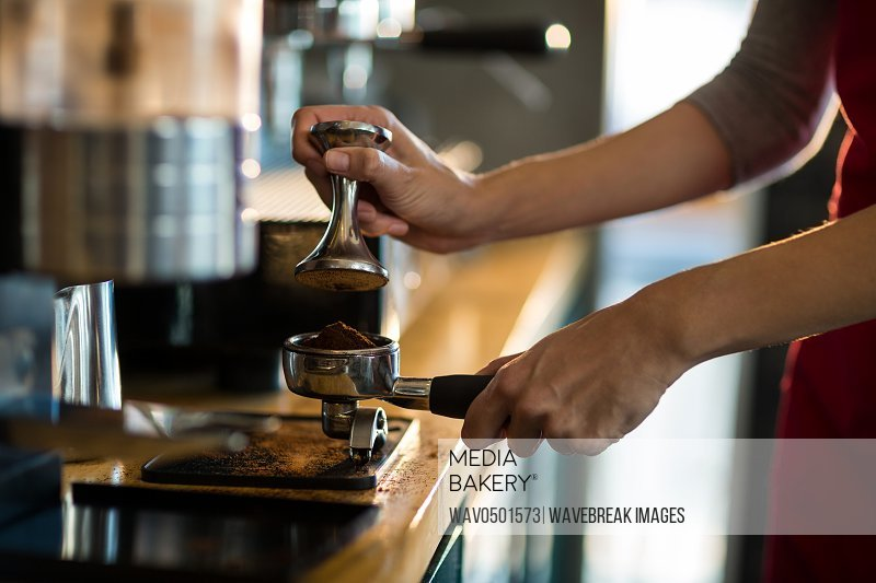 Waiter using a tamper to press ground coffee into a portafilter in cafA?