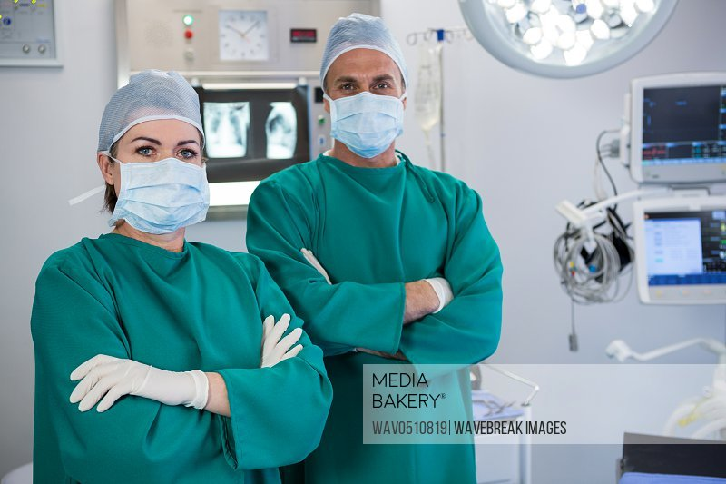 Portrait of surgeons standing in operation theater of hospital