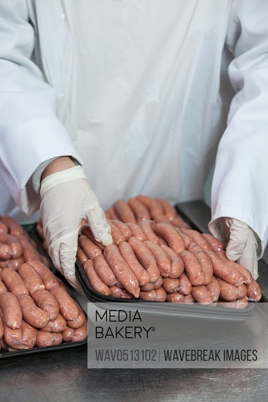 Butcher packing raw sausages