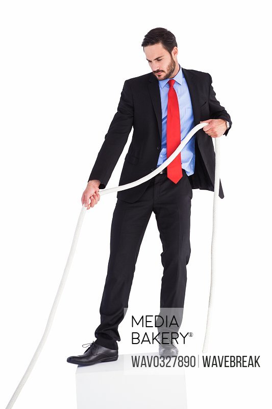 Businessman pulling a rope with effort