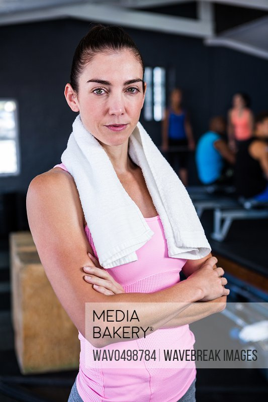 Portrait of confident athlete with arms crossed while standing in gym