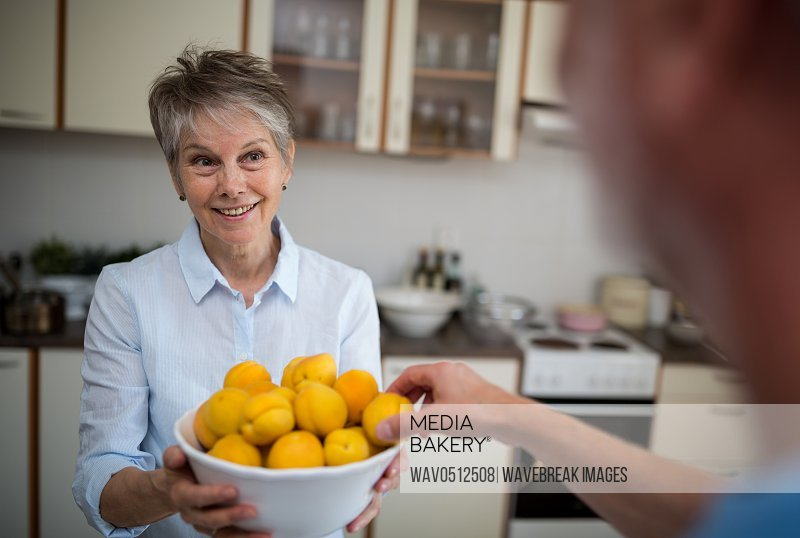 Senior woman holding a bowl of apricot in kitchen