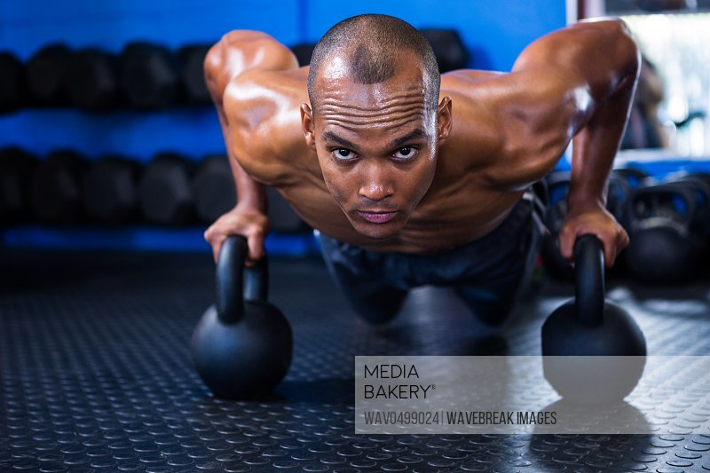 Portrait of determined man doing push-ups with kettlebells in gym