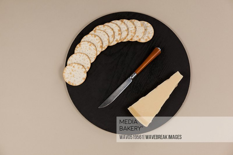 Slice of cheese with crispy biscuits and knife