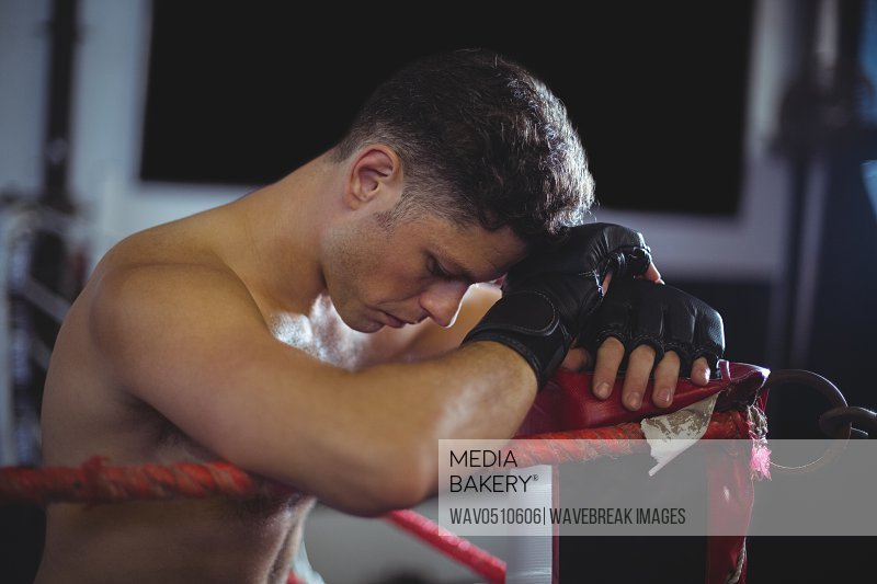 Tired boxer leaning on boxing ring
