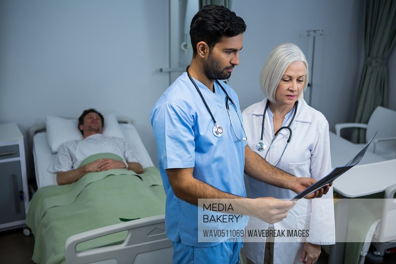 Surgeon and doctor discussing x-ray while consulting patient in ward