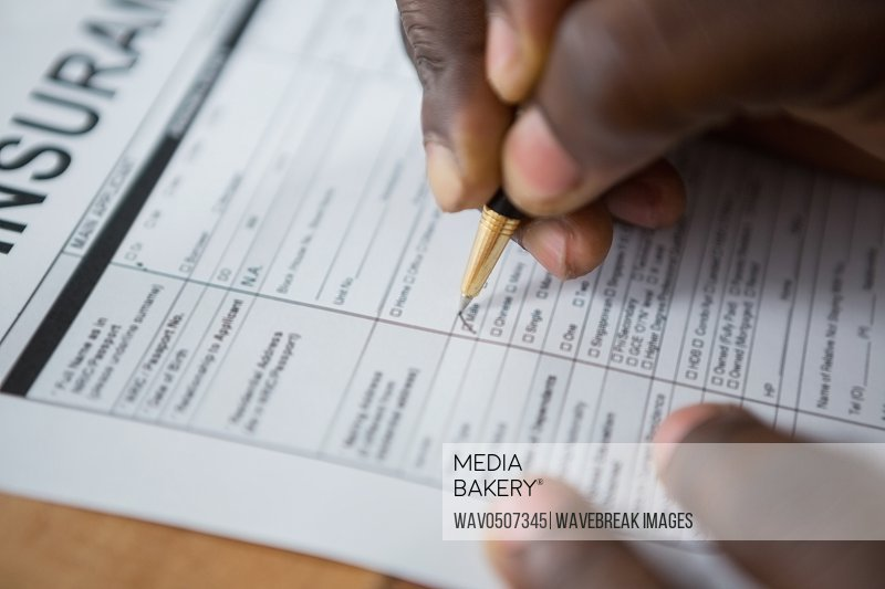 Close-up of mans hands signing insurance document at desk