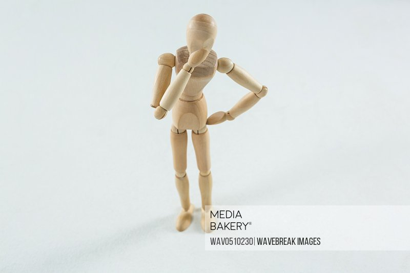 Tensed wooden figurine standing against white background