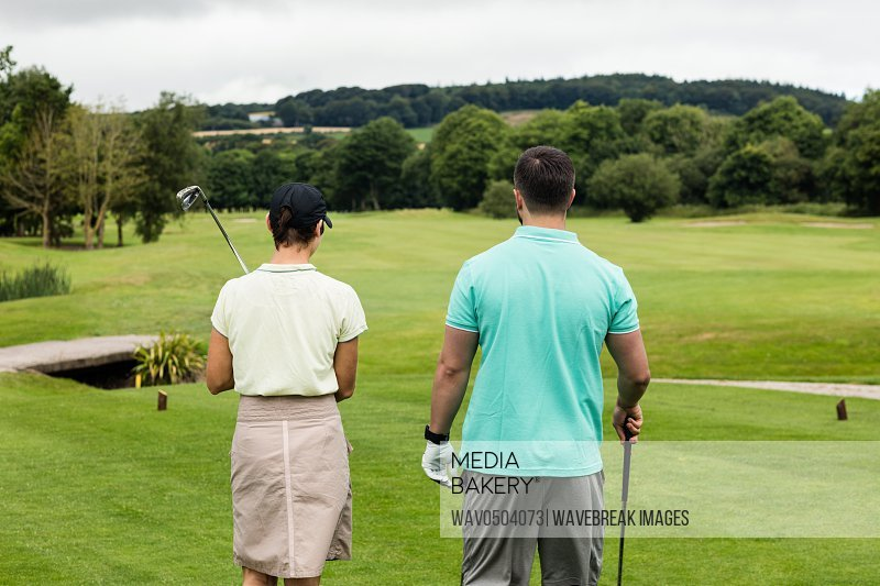 Rear view of couple standing on a golf course