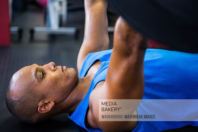 Side view of male athlete exercising with barbell in fitness studio