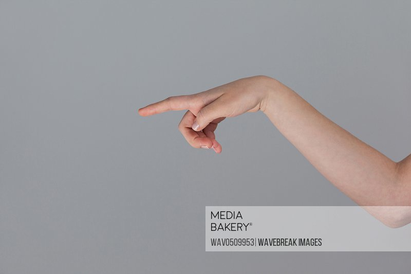 Hand of a woman pointing sideways against grey background