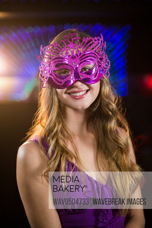 Portrait of smiling woman wearing masquerade in bar