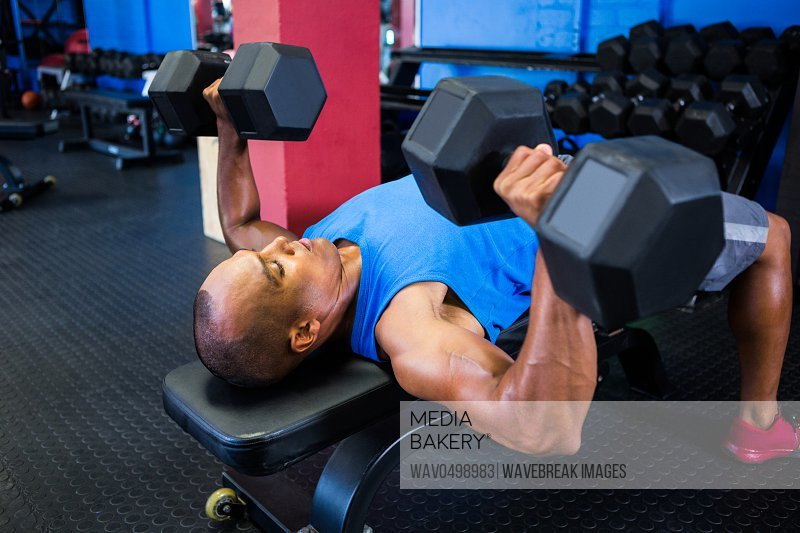 Male athlete exercising with dumbbells on weight bench in gym