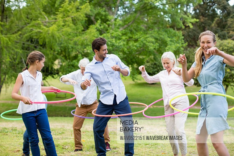 Multi-generation family playing with hula hoop