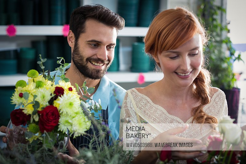 Happy couple arranging flowers in the flower shop