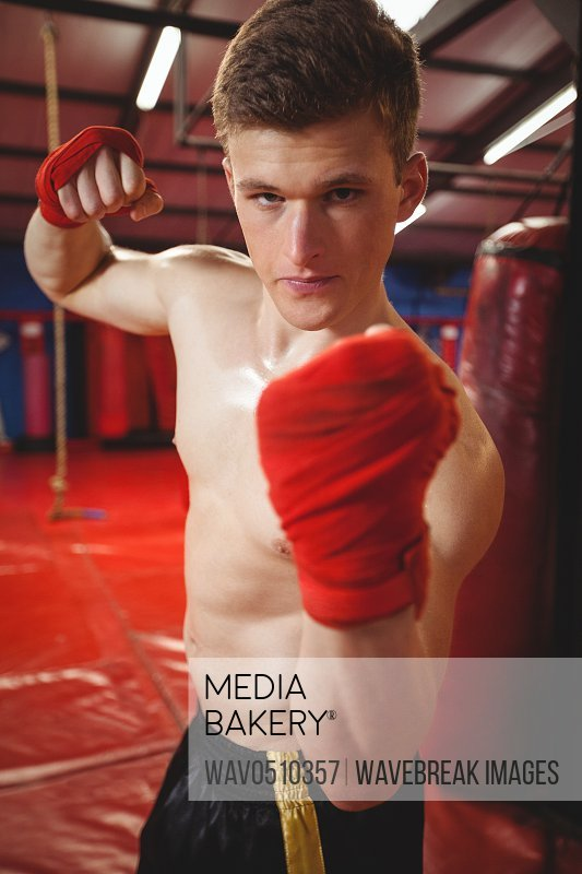 Portrait of a confident boxer punching in fitness studio