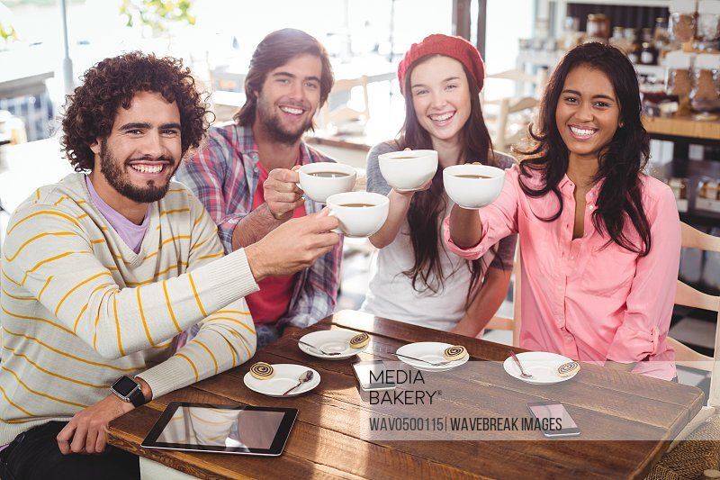 Group of happy friends holding cup of coffee in cafe