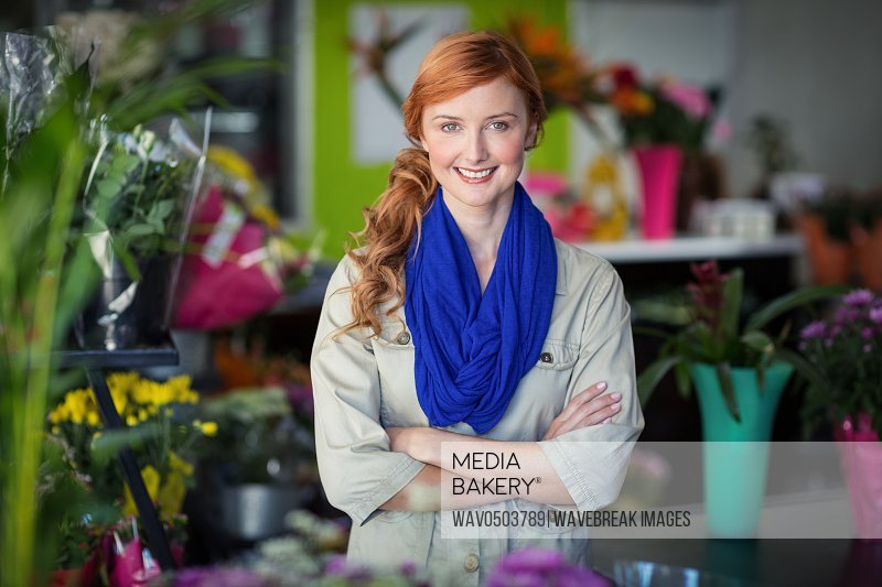 Portrait of happy florist standing with arms crossed in flower shop