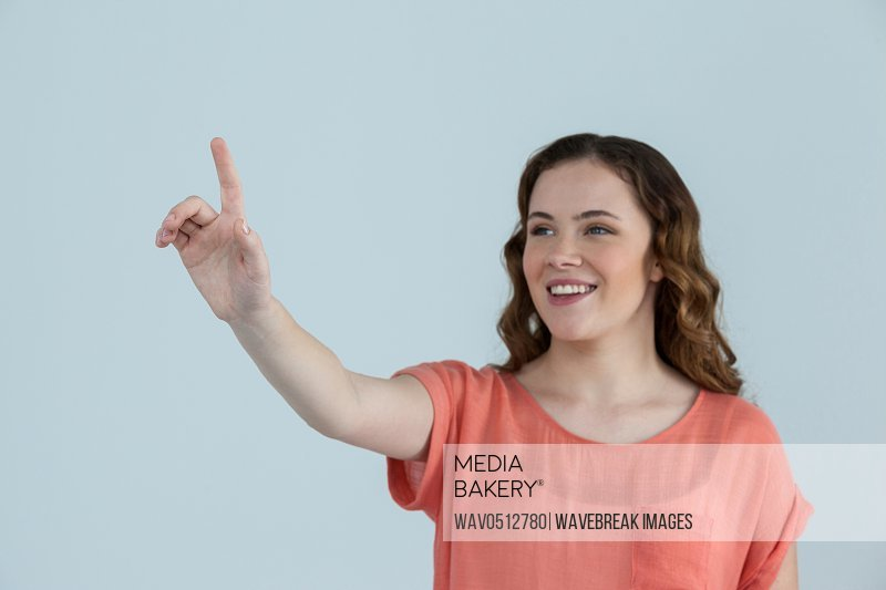 Woman pretending to touch an invisible screen against grey background