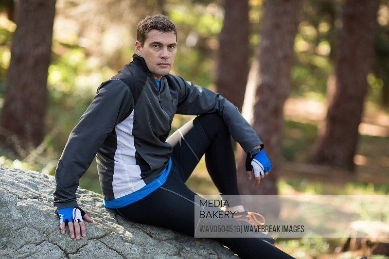 Portrait of male biker relaxing on rock in forest at countryside