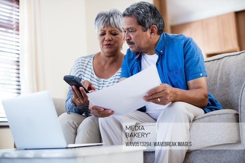 Senior couple checking bills in living room