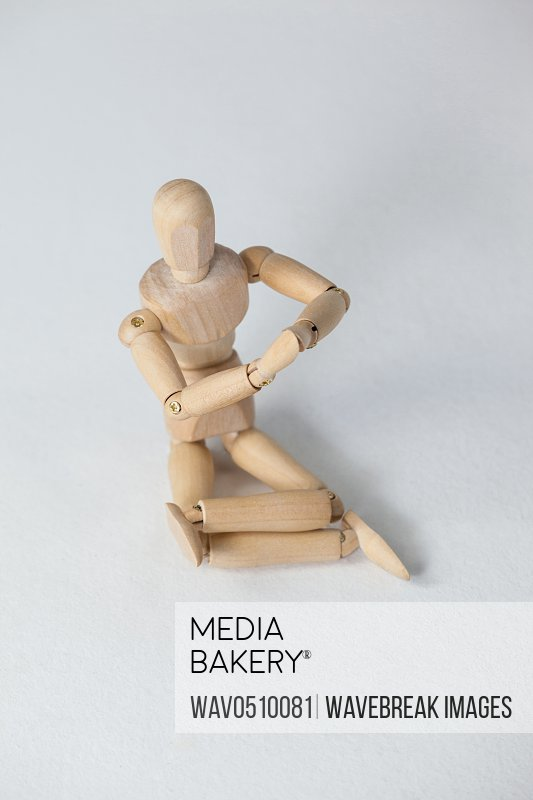 Wooden figurine performing yoga on floor against white background