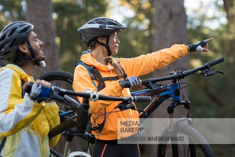 Biker couple carrying mountain bike and pointing in distance at countryside forest