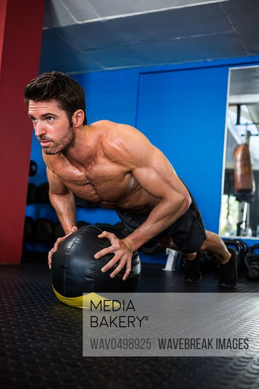 Young shirtless athlete exercising with ball in gym