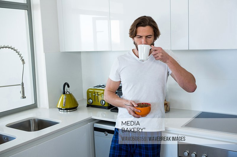 Man drinking coffee while having breakfast in kitchen at home