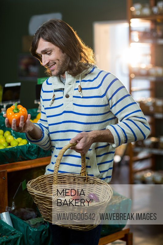 Man with a baskets selecting bell pepper in organic section of supermarket