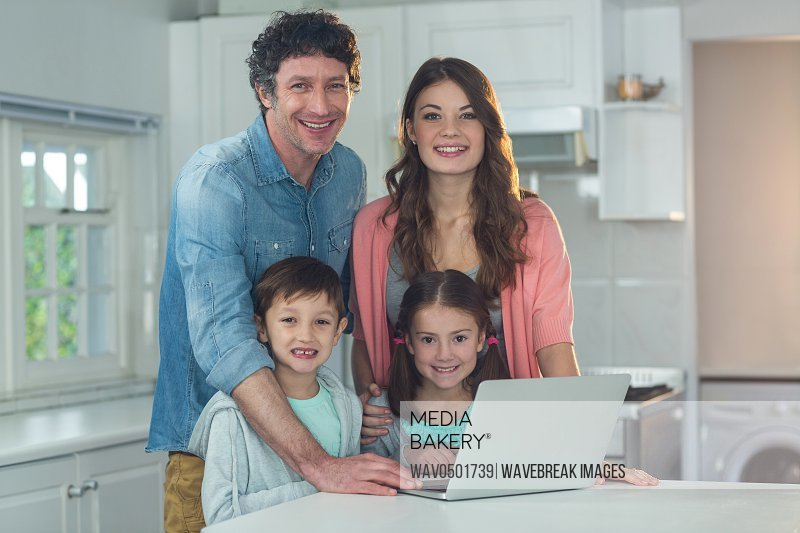 Portrait of happy family using laptop at home